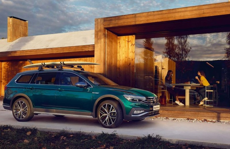 A green 2020 Volkswagen Passat, European station wagon version, parked outside a modern resort with a surfboard on its roof.
