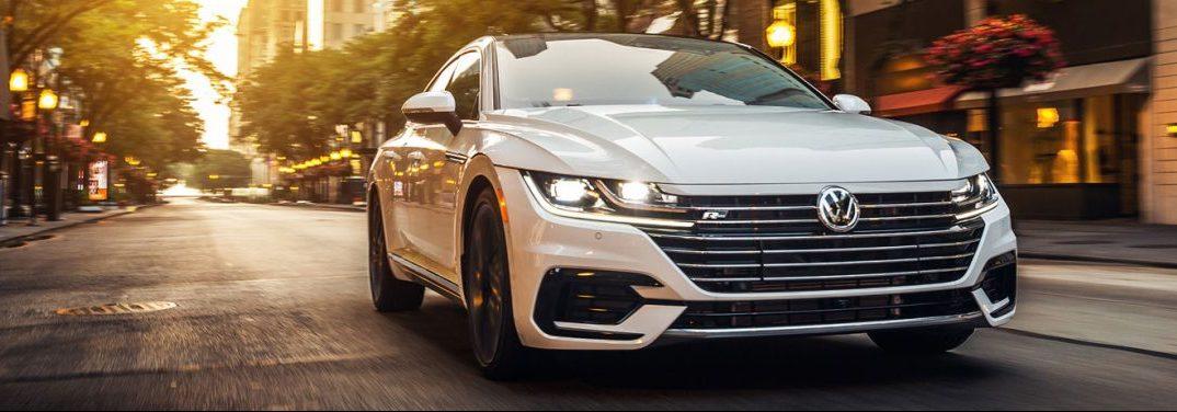 White 2020 Volkswagen Arteon cruises up a city street.