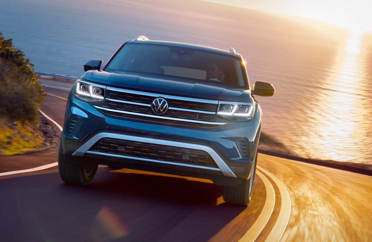 Head-on view of a 2021 Volkswagen Atlas winding up a seaside highway.