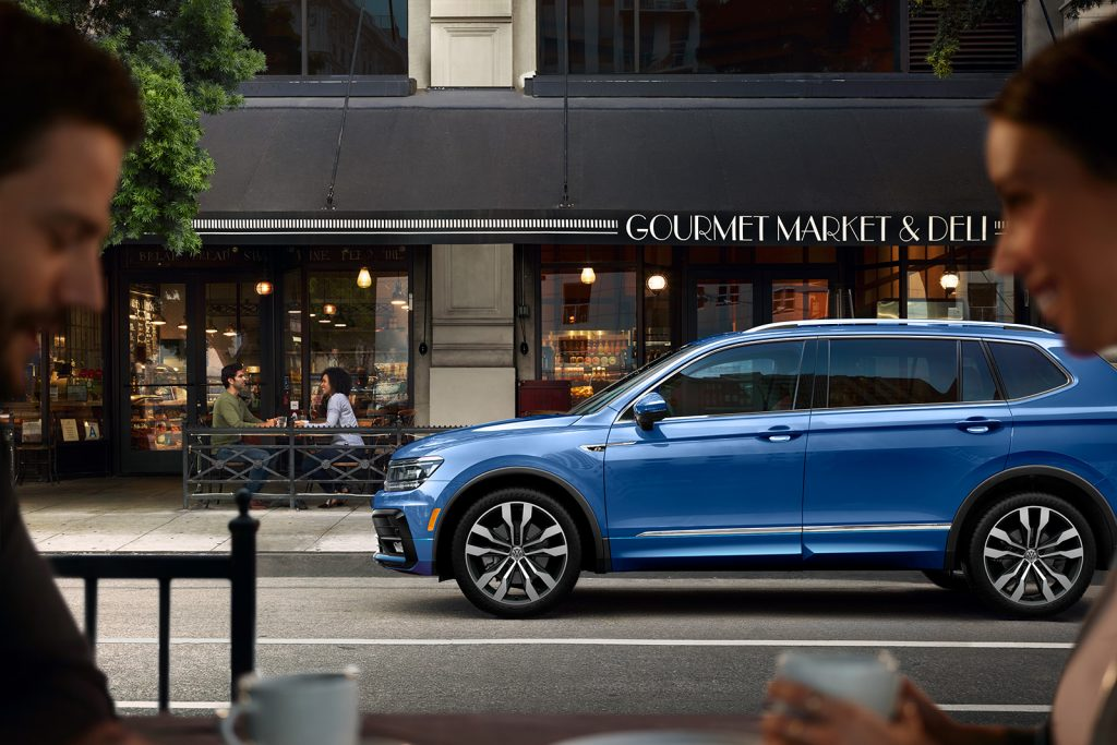 Side-view of a 2020 VW Tiguan driving by a fashionable cafe
