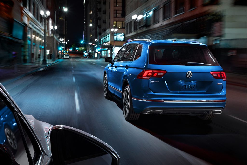 Blue 2020 Volkswagen Tiguan driving down a street at night