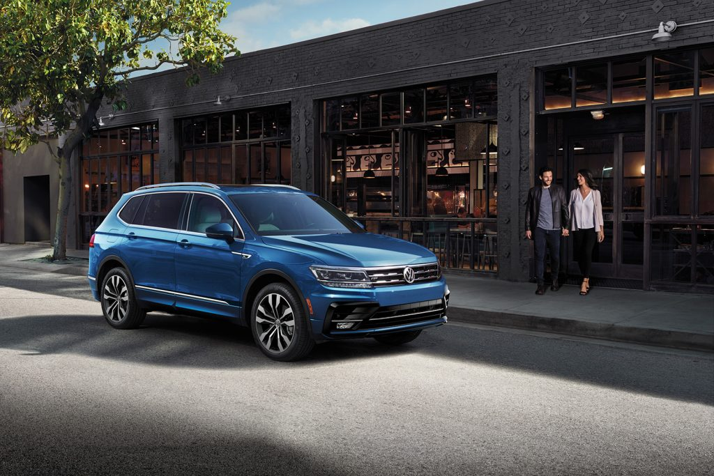 Blue 2020 Volkswagen Tiguan driving by a shop