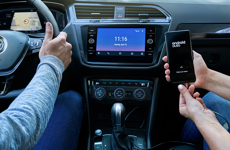 Woman plugs a smartphone into the Android Auto-equipped infotainment system