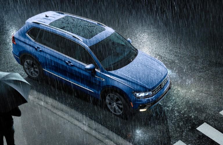 Blue 2020 Volkswagen Tiguan parked at a crosswalk in the rain