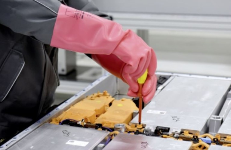 A person in pink gloves using a tool to take EV batteries apart