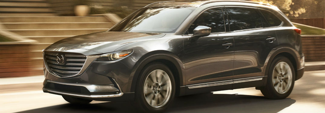 2018 Mazda CX-9 Family-Friendly Features with image of the CX-9 driving through a neighborhood