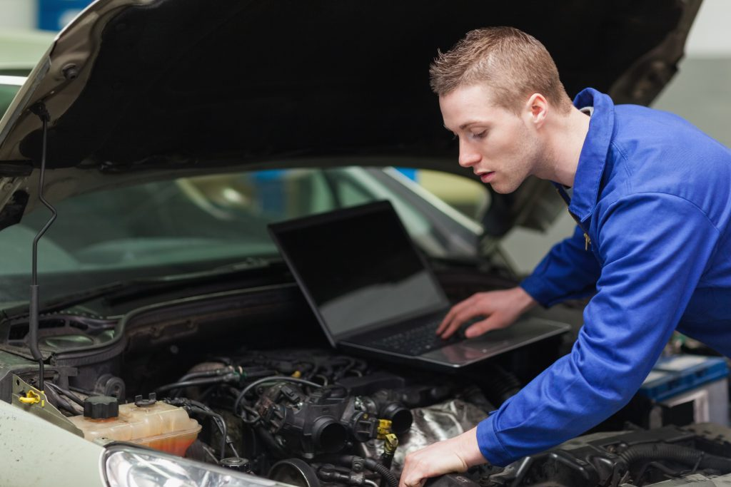 mechanic inspecting an engine with a laptop