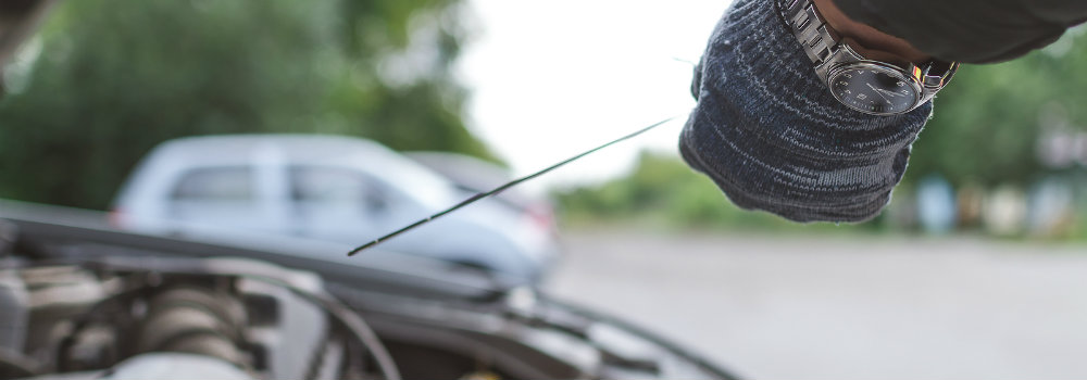 Mechanic using dipstick to check vehicle oil