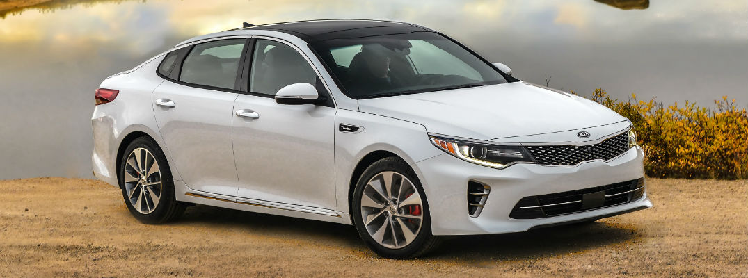 White 2018 Kia Optima Front and Side Exterior with Water in background