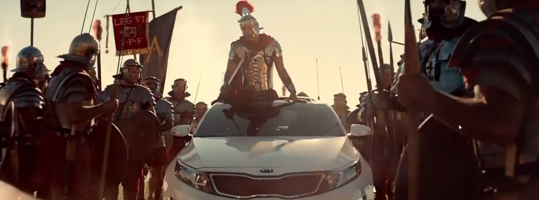 Basketball Star Blake Griffin Standing up Through Moonroof of Kia Optima, with Roman Army