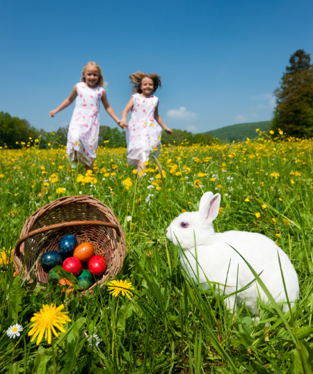 Two Kids Running Towards a White Rabbit and a Basket of Easter Eggs
