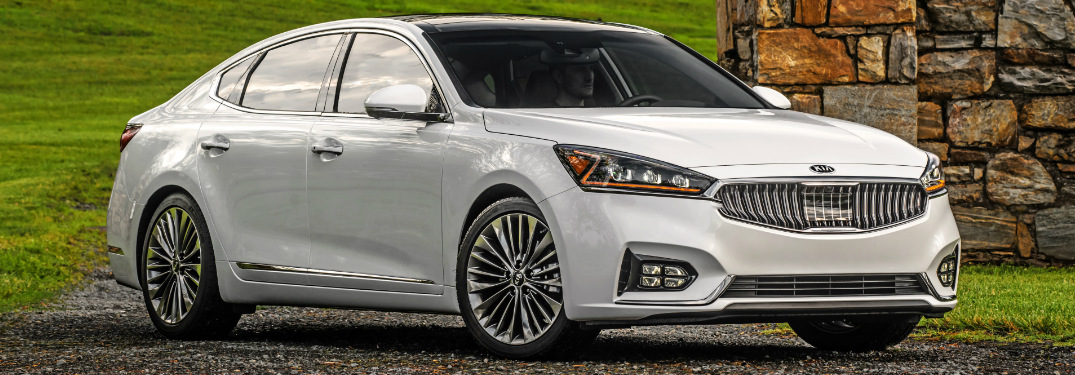 White 2018 Kia Cadenza with a Grassy Hill in the Background