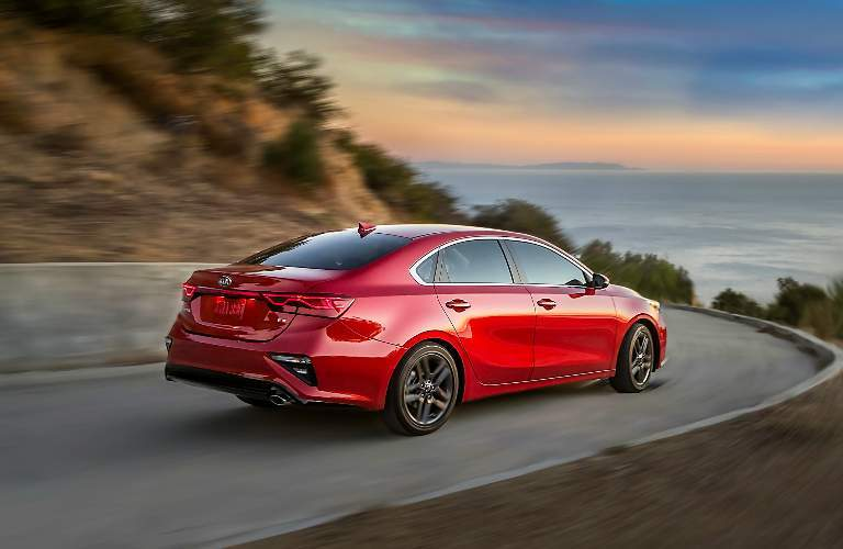 Red 2019 Kia Forte Driving on a Coastal Highway