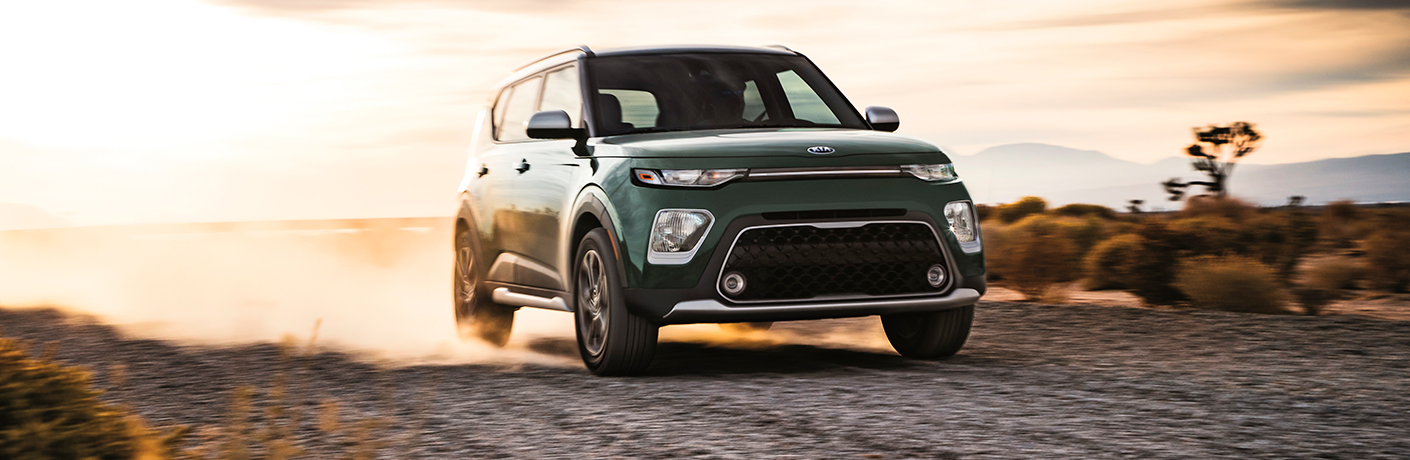 Green 2020 Kia Soul driving on a gravel road