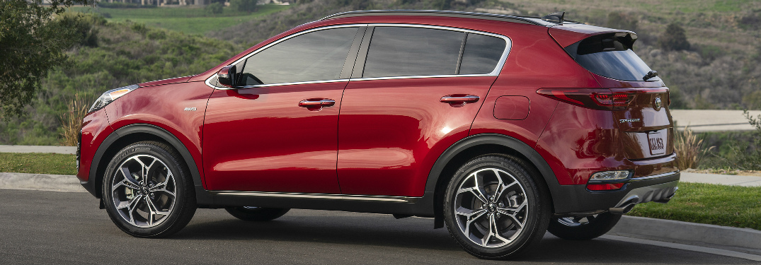 Red 2020 Kia Sportage parked near a forested area