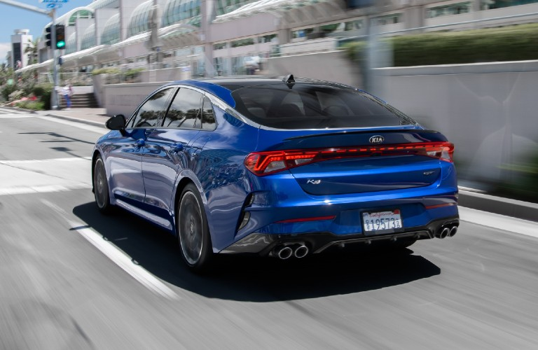 Driver's side rear angle view of blue 2021 Kia K5 GT