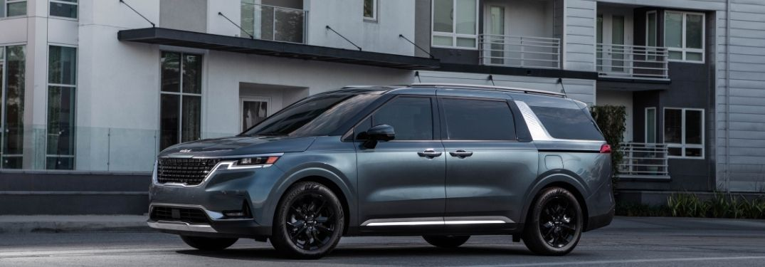 2022 Kia Carnival exterior driver side profile in front of building
