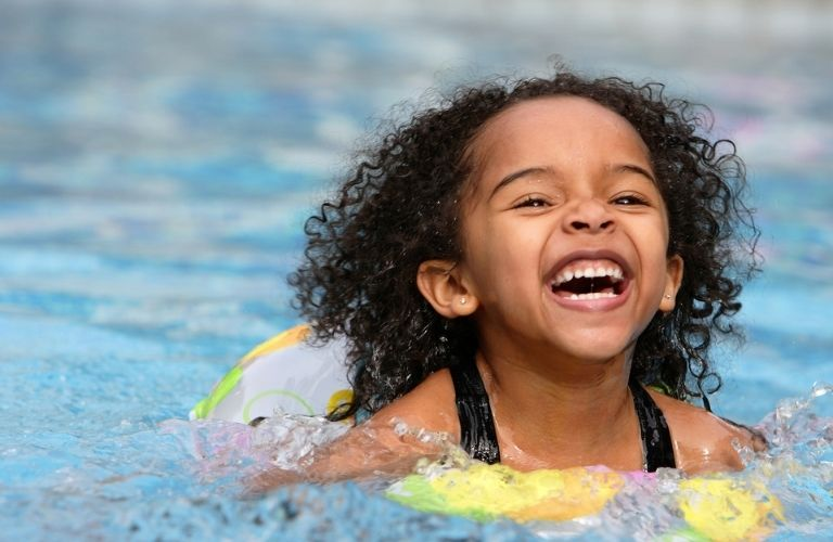 grinning child playing in water