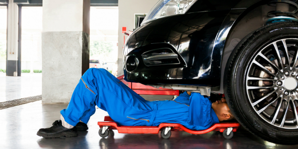 Technician Lying underneath a Car to Work