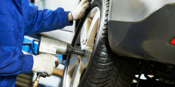 Technician Using an Impact Wrench on Lug Nuts