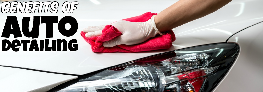 Person hand wiping white car clean with text of benefits of auto detailing
