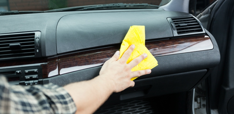 person hand dusting interior of a car