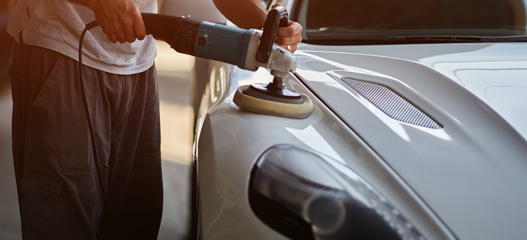 person polishing a white sports car