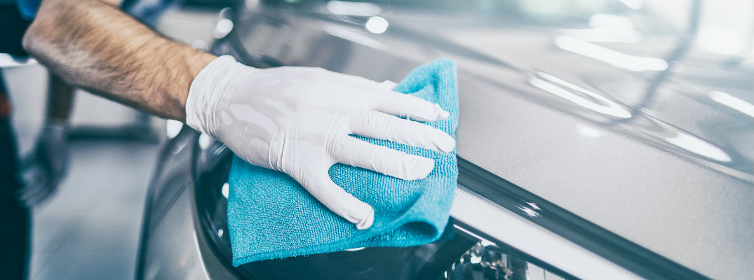 Gloved hand with a blue towel hand drying a car