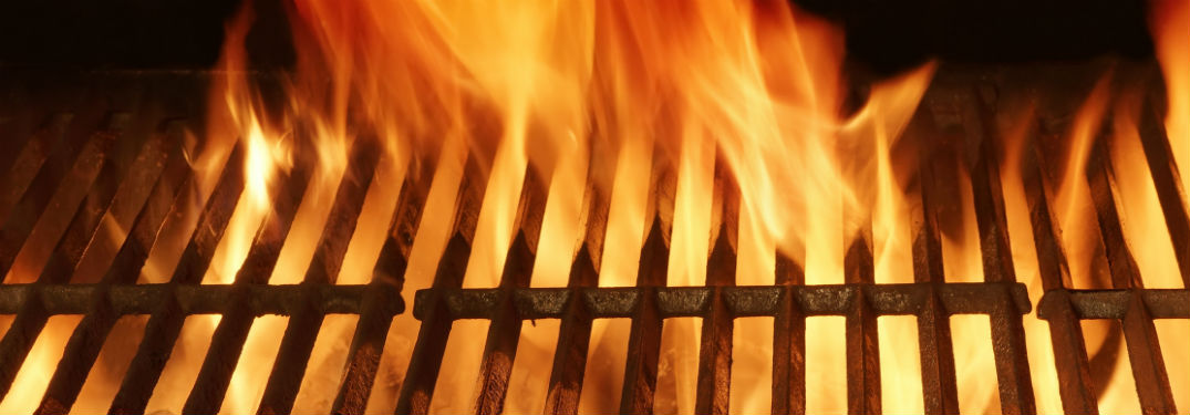 empty close up of grates on a flaming grill