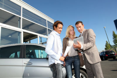 car salesmen looking at documents with couple