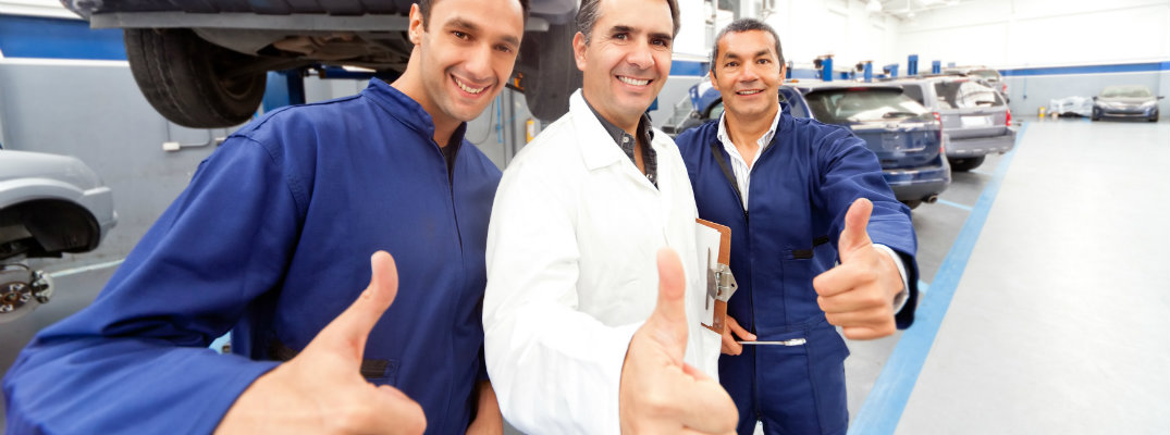 Three mechanics posing and giving thumbs up in a maintenance center