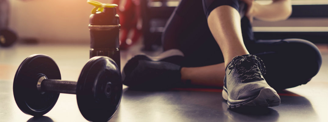 Woman sitting in gym area next to dumbbell and water bottle