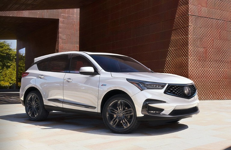 White 2020 Acura RDX parked in front of a brick building.