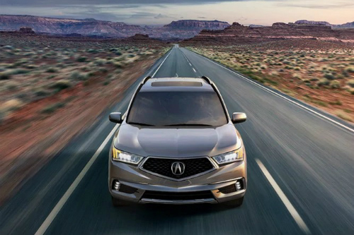 2020 Acura MDX Sport Hybrid drives down a desert highway toward the camera.