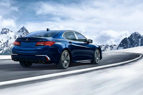 Blue 2020 Acura TLX goes around a curve in an intensely snowy environment.