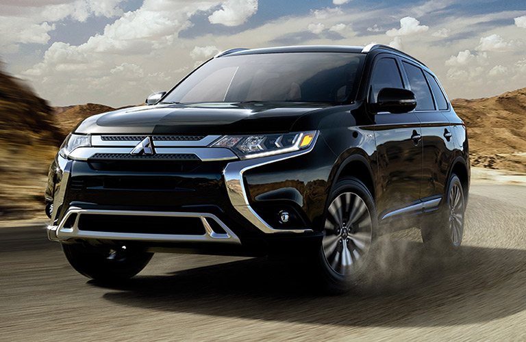 Dark-colored Mitsubishi Outlander rolls around a highway out in a desert.