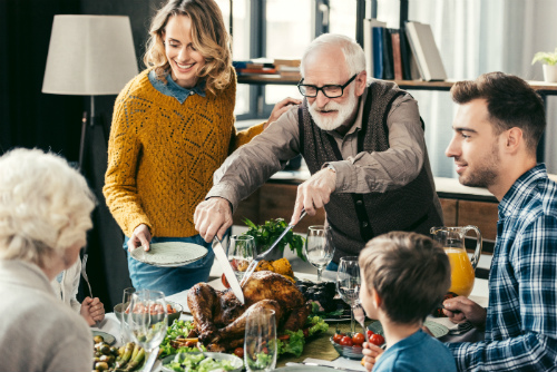 family at thanksgiving table with elderly man carving turkey