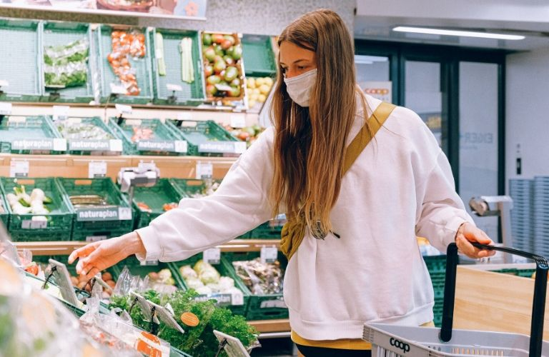 A woman grocery shopping while wearing a mask, presumably in Chicago.