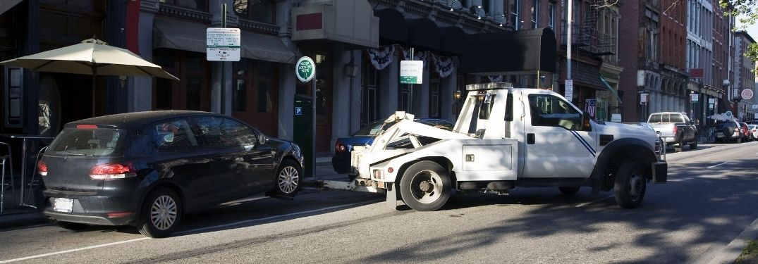 Hatchback car being towed in city