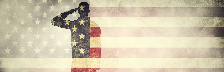 silhouette of American soldier behind American flag