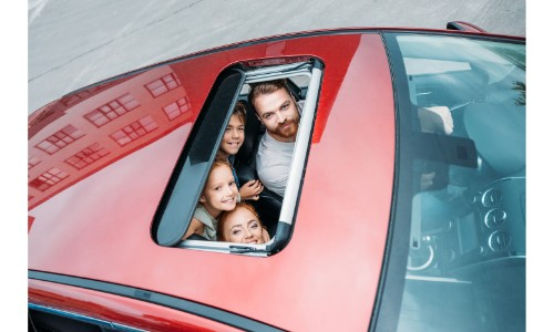 Family of four staring up out of red sunroof