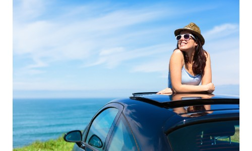 Woman in sun hat by the beach standing up out of sun roof