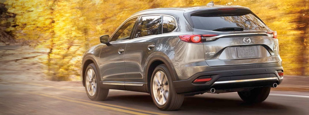 Rear shot of 2019 Mazda CX-9 driving on tree-lined autumn road
