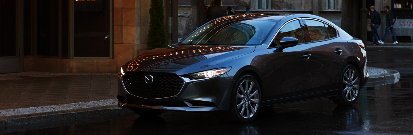 Blue 2019 Mazda3 drives down a dark street.