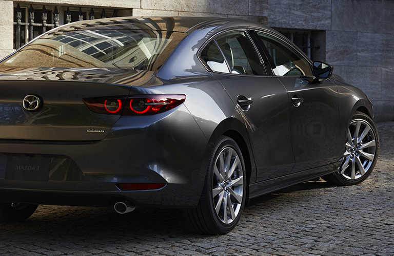 Silver 2019 Mazda3 making a U-turn in a concrete alleyway of what could be a seaside Italian town.