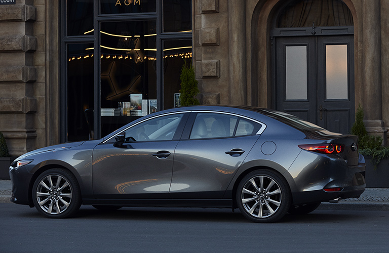 Silver 2019 Mazda3 sedan parked in front of an old building. Side-view.