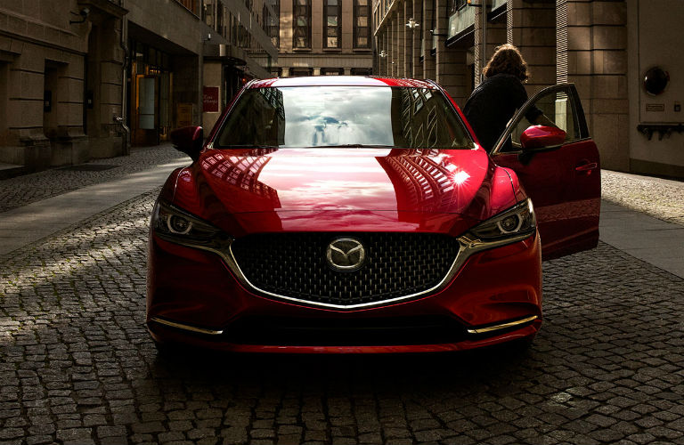 Head-on view of a red 2019 Mazda6 parked in a city as a woman emerges from the driver's seat.