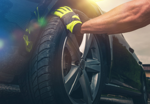 A gloved hand is presses its palm solidly against the tire of a blue car.