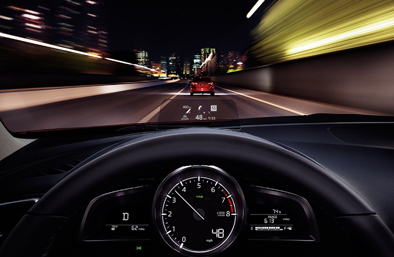First-person view driving a 2018 Mazda3 down a highway at night with a HUD equipped.