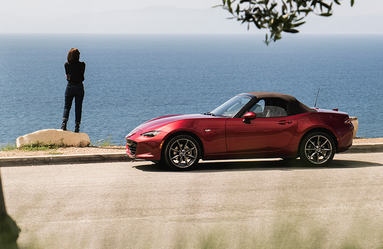 A woman stands beside a parked red 2019 Mazda MX-5 Miata and gazes wistfully out to sea.